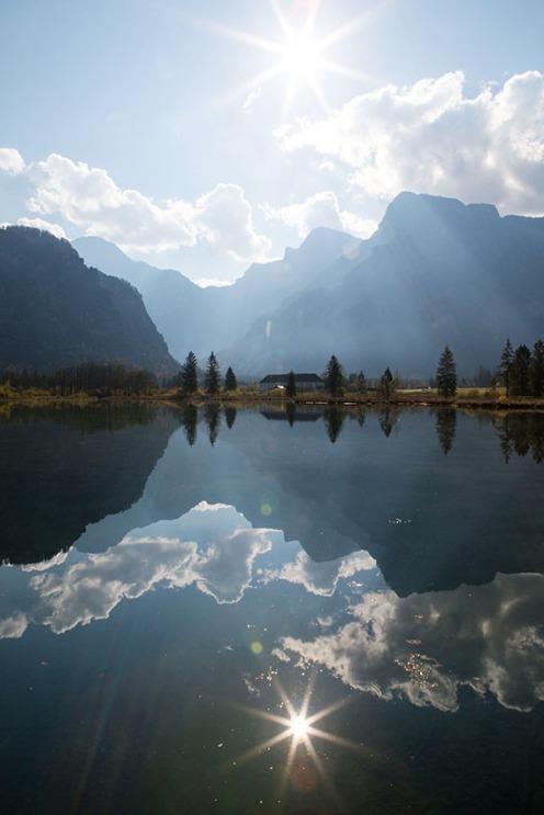 Herbststimmung am Almsee in Oberösterreich! Sonne, Wolken und Berggipfel spiegeln sich klaren Seewasser.