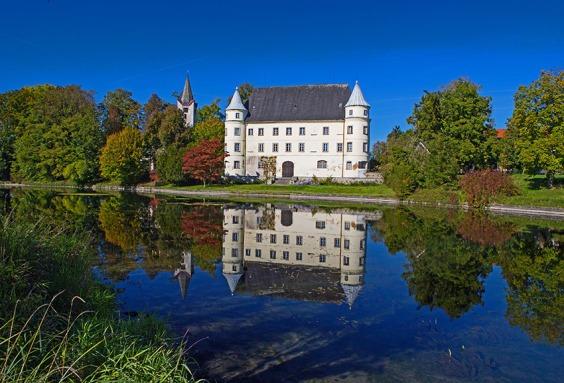 Das Bild zeigt Schloss Hagenau im Bezirk Braunau mit Spiegelbild in einem Seitenarm des Inn-Stausees im Umweltschutzgebiet Unterer Inn. Foto: rubra